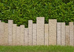 Moderne Gartenmauer aus Granitsulen und Hecke